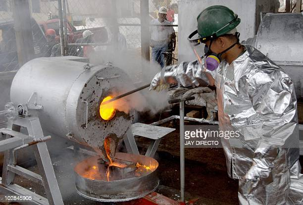 A Filipino mill worker of Canadian miner TVI Pacific wearing a heat protection suit pour a molten mixture of gold and silver bullion mold at the end...