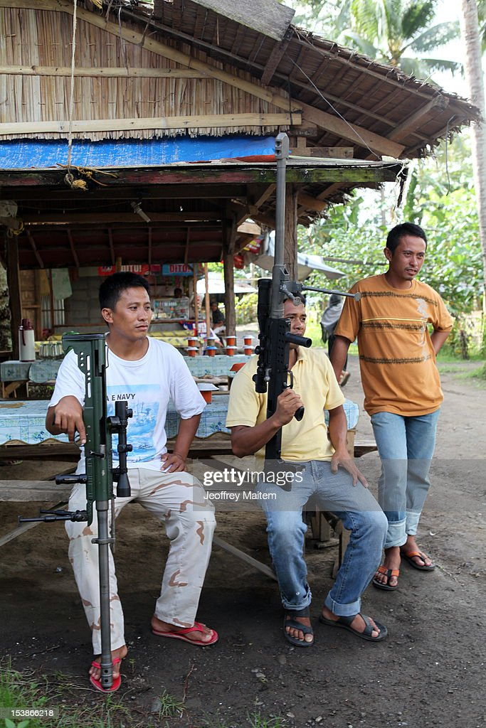 Filipino Muslim rebels sit with their barrett weapons inside a rebel camp on October 10, 2012 in Sultan Kudarat township, southern Philippines. President Benigno Aquino claimed the latest development in the negotiation with the rebels is a major milestone after decades of militant insurgency in the nation's troubled south. Both parties are expected to sign the peace agreement on October 15, 2012.
