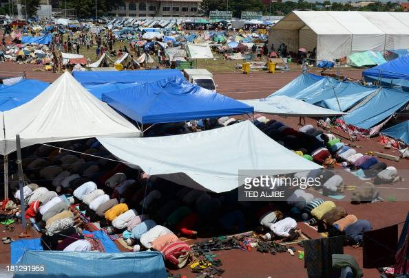 Filipino Muslims affected by the standoff between Philippine government forces and Muslim rebels pray during Friday prayers at a tent serving as a...