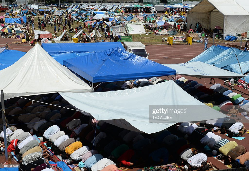 Filipino Muslims affected by the stand-off between Philippine government forces and Muslim rebels pray during Friday prayers at a tent serving as a makeshift prayer room inside an evacuation center at a sports complex in Zamboanga on the southern Philippine island of Mindanao on September 20, 2013. Philippine security forces killed eight Muslim rebels on September 20 as they hunted the remnants of a guerrilla force hiding in homes of the major city and believed to be holding hostages.