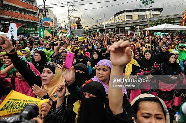Filipino Muslims cheer outside the presidential palace after the conclusion of the signing of the Comprehensive Agreement on the Bangsamoro between...
