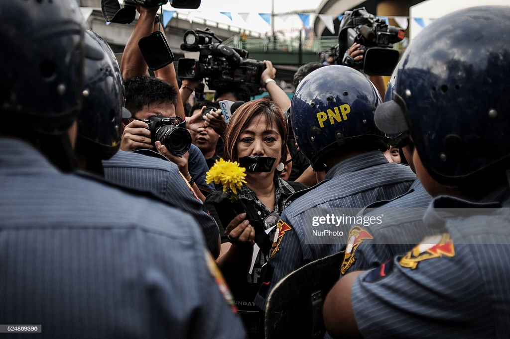 A Filipino netizen offers flowers to policemen during a demonstration versus a new law making online libel a criminal offence at the EDSA Shrine in...
