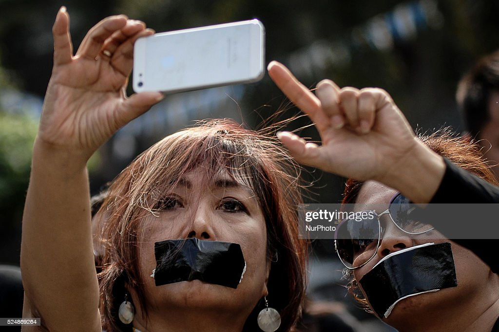 Filipino netizens with tape over their mouths take a selfie during a demonstration versus a new law making online libel a criminal offence at the...