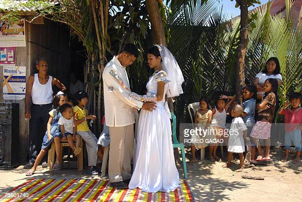 Filipino newlyweds Richard Laureo and Adema Rapsing with cash gifts pinned on their wedding clothes by relatives dance in the street outside the...