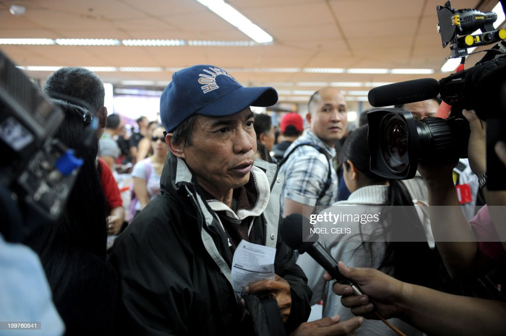 A Filipino overseas worker (C) is interviewed by the press upon his arrival at Manila International Airport on January 20, 2013 after being sent home by his employer in Algeria due to security fears following an Islamic militant attack at a remote gas plant. Many of the 39 returnees said they worked for a British energy facility hundreds of kilometres from the In Amenas gas plant that was attacked by the militants last week. AFP PHOTO / NOEL CELIS