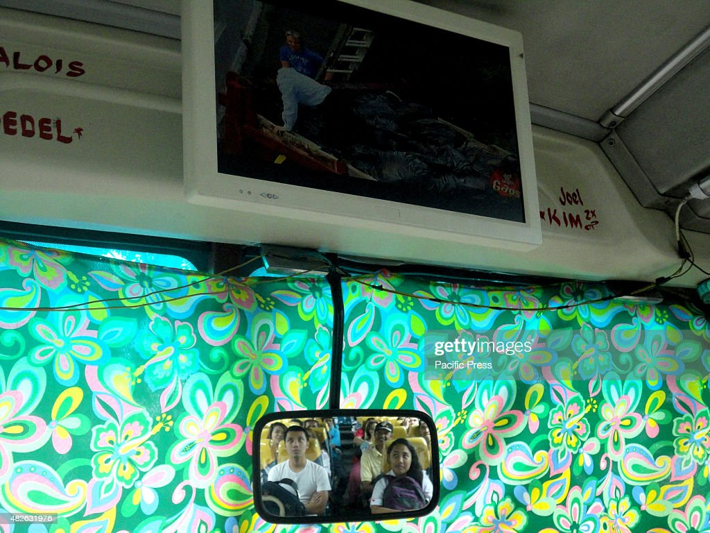 Filipino passengers reflected by the rearview mirror below watch a comedy skit shown at a bus travelling in Caloocan City
