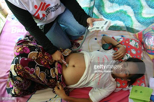Filipino physician from Doctors Without Borders examines a Muslim pregnant woman during their visit in one of evacuation camps on September 30 2009...