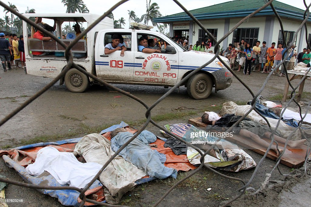 Filipino policemen look at the bodies of flood victims at the compound of municipal gymnasium on December 5, 2012 in the southern Philippine township of New Bataan, Compostela province, Philippines. More than 100 people have been killed and scores of others remain missing after Typhoon Bopha, the strongest storm to hit the Philippines this year, pounded the region.