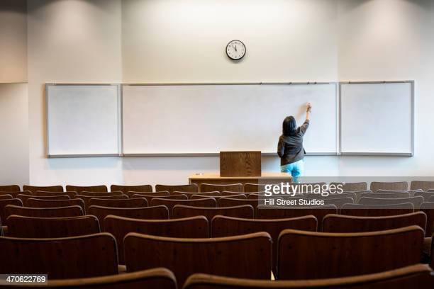 Filipino professor writing on whiteboard in empty lecture hall