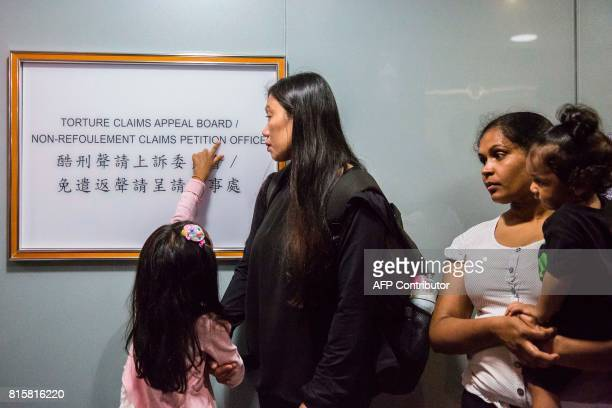 Filipino refugee Vanessa Rodel with her daughter Keana and Sri Lankan refugee Nadeeka Nonis with her baby boy Dinath wait outside an office of the...