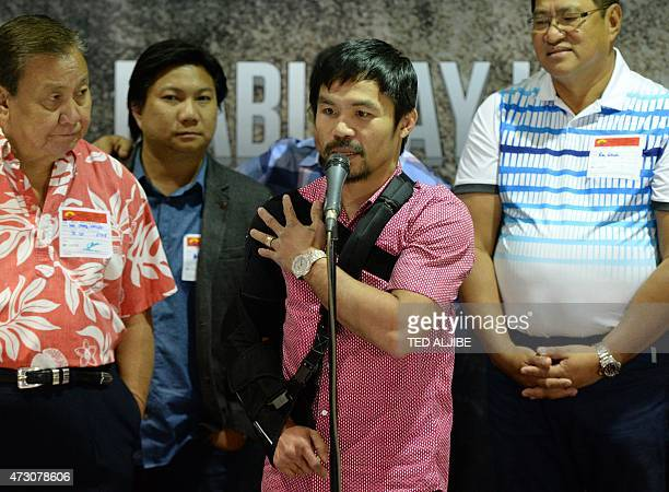 Filipino ring icon Manny Pacquiao touches his injured right shoulder during a press conference shortly after arriving from the US at the...