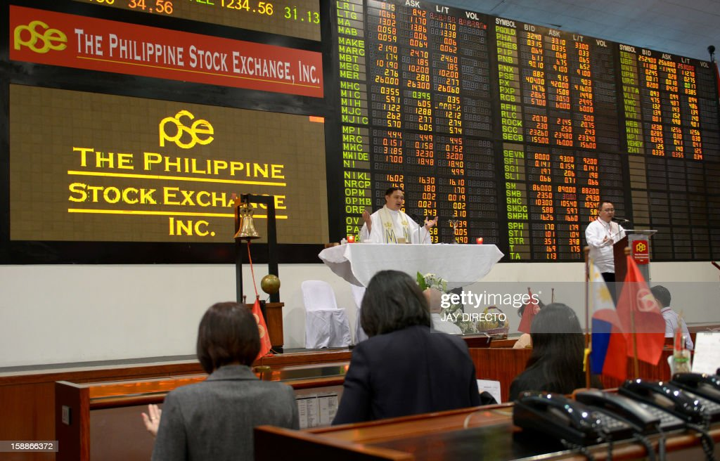 A Filipino Roman Catholic priest (C) officiates a mass in front of the electronic board to mark the first day of trading of the new year at the Philippine Stock Exchange in Manila on January 2, 2013. Philippine share prices closed 0.83 percent higher, up 48.26 points to close at 5,860.99, to a new all-time high on rising optimism that the US fiscal cliff would be averted, dealers said.