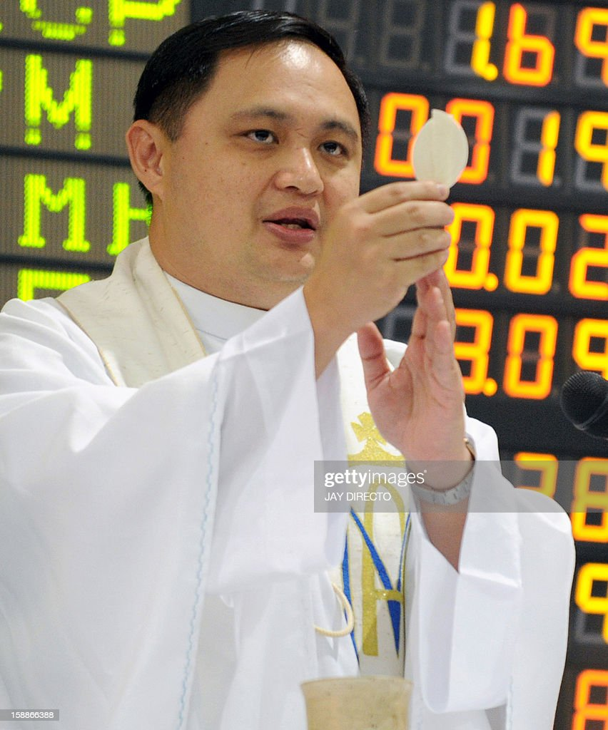 A Filipino Roman Catholic priest officiates a mass in front of the electronic board to mark the first day of trading of the new year at the Philippine Stock Exchange in Manila on January 2, 2013. Philippine share prices closed 0.83 percent higher, up 48.26 points to close at 5,860.99, to a new all-time high on rising optimism that the US fiscal cliff would be averted, dealers said.