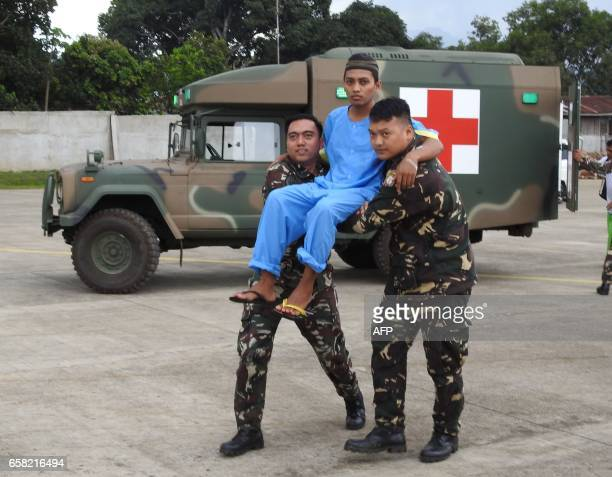 Filipino soldiers carry one of three rescued Malaysian hostages to a waiting aircraft at the airport in Jolo town sulu province in southern island of...