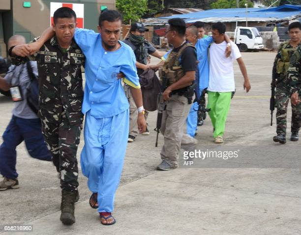 Filipino soldiers help and escort rescued Malaysian hostages to a waiting aircraft at the airport in Jolo town sulu province in southern island of...