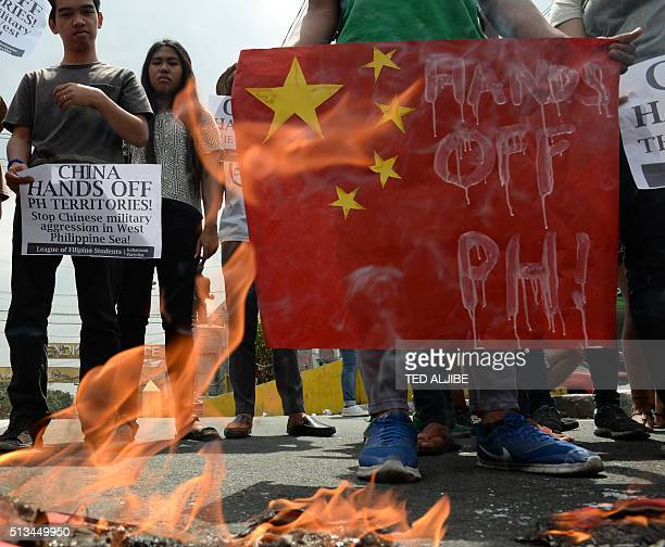 Filipino students stand next to a burning replica of Chinese maritime surveillance ships as they hold a rally near Malacanang Palace in Manila on...