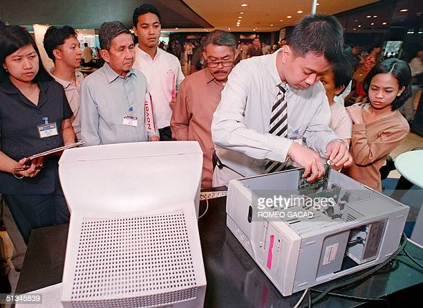 Filipino technician installs an Americanmade Cybergeddon PC enhancement card in a computer to demonstrate its features in eliminating the Y2K...