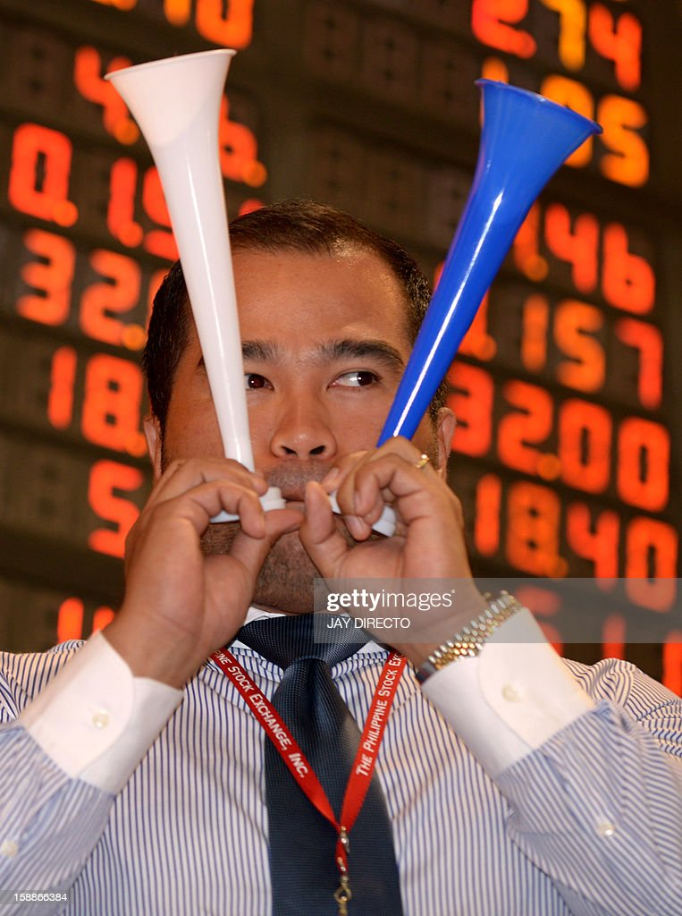A Filipino trader blows a horn to mark the first trading day of the year at the Philippine Stock Exchange in Manila on January 2, 2013. Philippine share prices closed 0.83 percent higher, up 48.26 points to close at 5,860.99, to a new all-time high on rising optimism that the US fiscal cliff would be averted, dealers said.