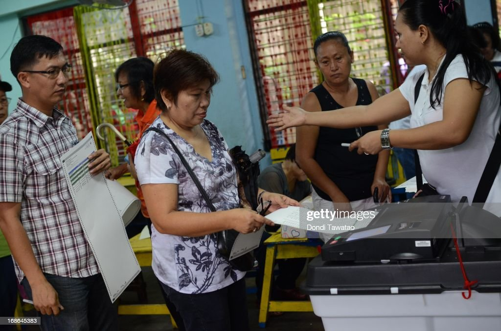 A Filipino voter slides her voting paper into a Precint Count Optical Scanner (PCOS) machine at an elementary school converted into a polling station on May 13, 2013 in Manila, Philippines. Millions of Filipinos cast their vote for the midterm elections to determine their choice candidates for local and national posts including senatorial and congressional posts for the Upper and Lower House of the Philippine Congress. So far, over 50 people have been killed in the run up to polling day for the elections that have been marred by violence and accusations of corruption and neopotism.