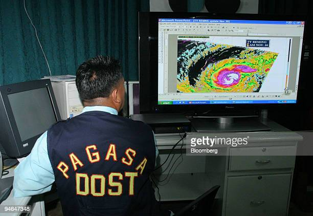 Filipino weatherman points to the eye of Supertyphoon Durian seen in the satellite image passing over the Island of Catanduanes in the Philippines on...