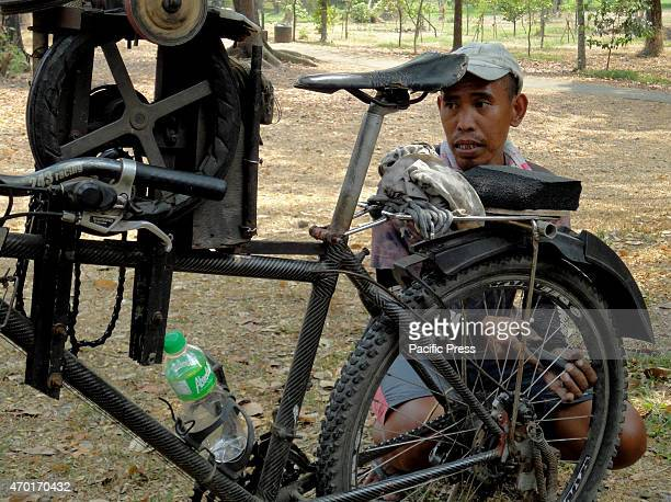 Filipino who works as a blade sharpener uses a pump to fill a bicycle tire with air at the University of the Philippines in Diliman district Blade...