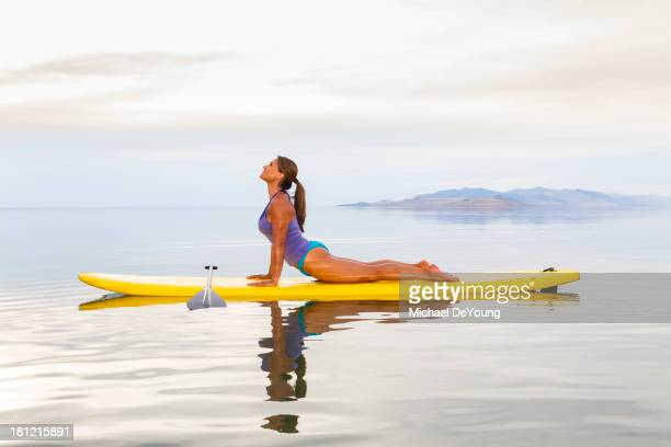 Filipino woman practicing yoga on paddle board