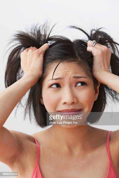 Filipino woman pulling hair and looking stressed