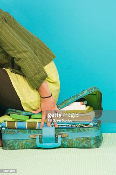 Filipino woman trying to close suitcase