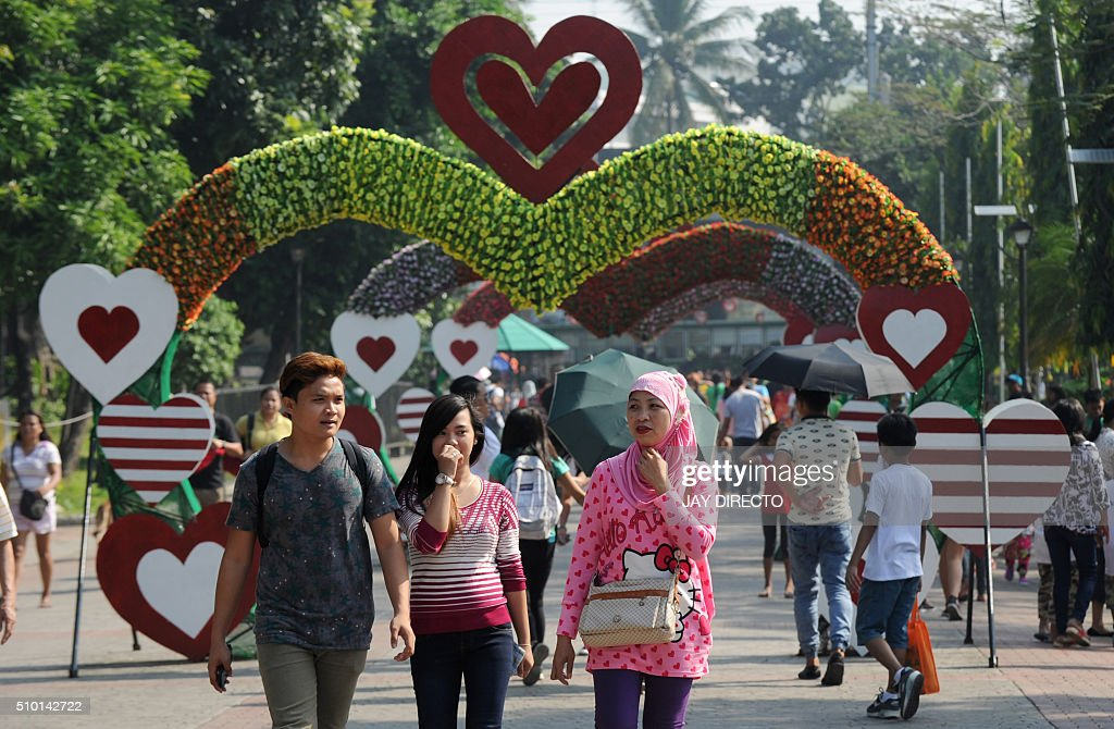 Filipino youths walk past a giant heart-shaped arch set up in Manila's Rizal Park to mark Valentine's Day on February 14, 2016. Although not an official holiday, Valentine's Day is widely celebrated in this largely Christian nation with acts of affection and romance such as sweethearts going on special dates or giving expensive presents. AFP PHOTO / Jay DIRECTO / AFP / JAY DIRECTO