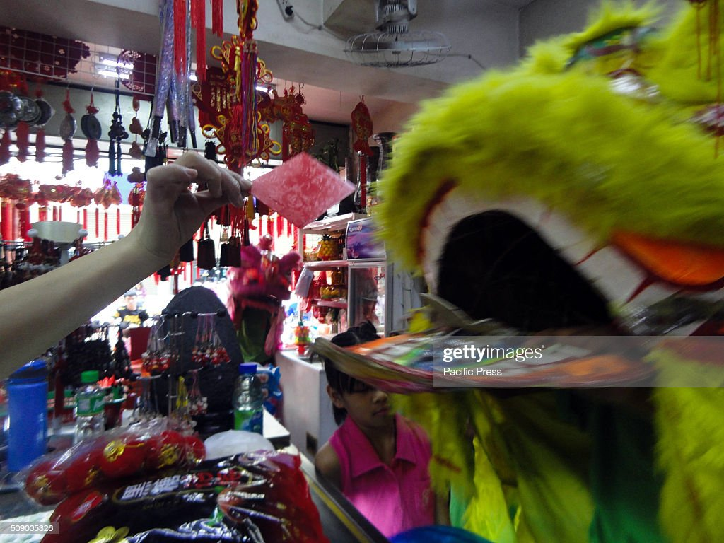 Filipino-Chinese storekeeper, left, hands a red envelope called 'ang bao' to a dragon dance performer inside a store in Manila's Chinatown. This year marks the Year of the Fire Monkey in Chinese astrology.