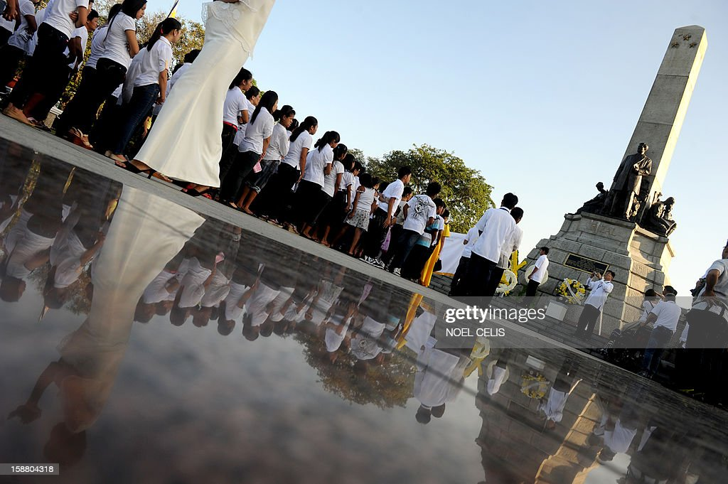 Filipinos queue up to pay their respects at the monument of Philippine national hero Jose Rizal during a ceremony marking the 106th anniversary of his death at the Luneta Park in Manila on December 30, 2012. Rizal was sentenced to death by a firing squad of the Spanish army after he was accused of leading a revolution against Spain.