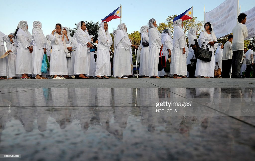 Filipinos queue up to pay their respects at the monument of Philippine national hero Jose Rizal during a ceremony marking the 106th anniversary of his death at the Luneta Park in Manila on December 30, 2012. Rizal was sentenced to death by a firing squad of the Spanish army after he was accused of leading a revolution against Spain. AFP PHOTO / NOEL CELIS