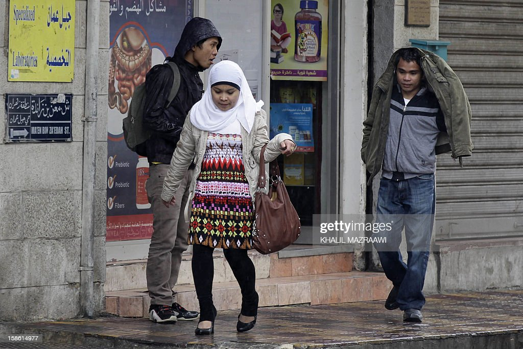 Filipinos residing in Jordan walk under the rain near central Amman on December 21, 2012. In October, the Philippines lifted a ban imposed in 2007 on its citizens working in Jordan after the two countries signed deals to protect them, including guaranteeing a minimum monthly salary of $400. The ban had been imposed because of 'the growing number of distressed Filipino workers' seeking help from diplomatic offices in Jordan, according to Manila. But despite the accords, abuse is still reported. AFP PHOTO/KHALIL MAZRAAWI