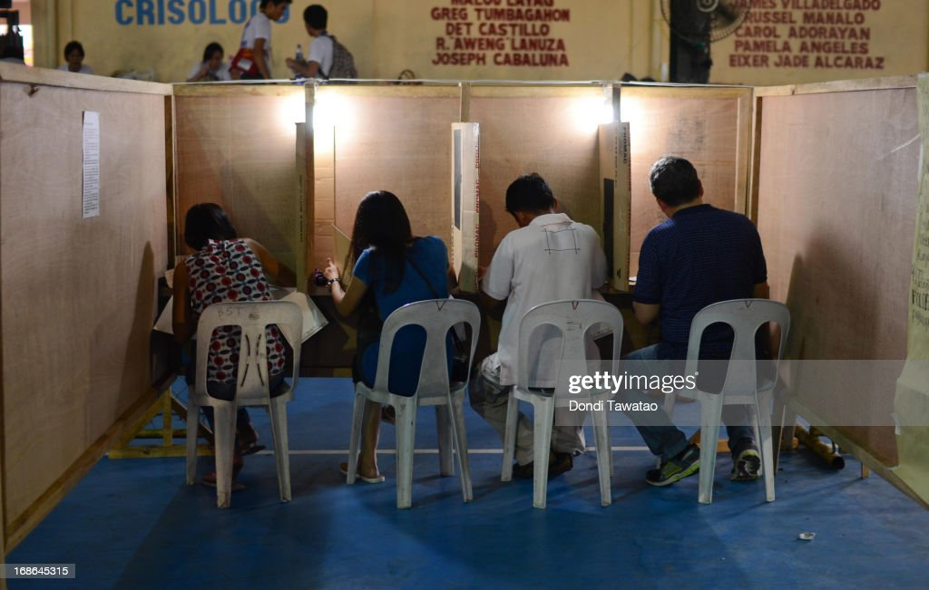 Filipinos vote at a public gymnasium converted into a polling station on May 13, 2013 in Manila, Philippines. Millions of Filipinos cast their vote for the midterm elections to determine their choice candidates for local and national posts including senatorial and congressional posts for the Upper and Lower House of the Philippine Congress. So far, over 50 people have been killed in the run up to polling day for the elections that have been marred by violence and accusations of corruption and neopotism.