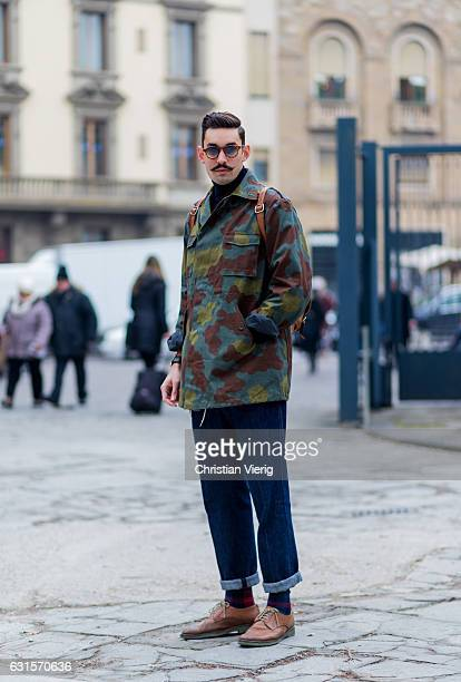 Filippo Bisa is wearing a camouflage jacket denim jeans leather shoes on January 12 2017 in Florence Italy