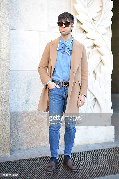 Filippo Fiora poses wearing a Caruso coat and Gucci shirt and belt before the Costume National show at Piazza del Duomo is seen during the Milan...