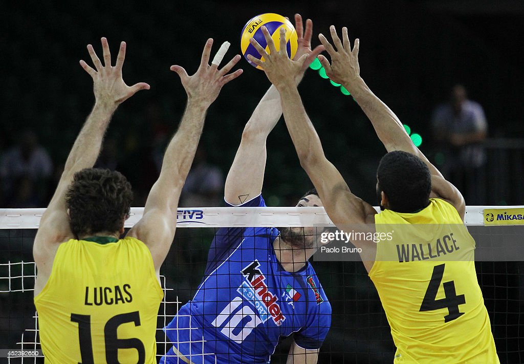 Filippo Lanza of Italy spikes the ball as Lucas Saatkamp and his teammate Wallace De Souza of Brazil block during the FIVB World League Final Six semifinal match between Italy and Brazil at Mandela Forum on July 19, 2014 in Florence, Italy.