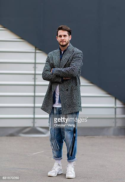 Filippo Serafini is wearing a grey checked coat denim jeans with patches white sneaker on January 12 2017 in Florence Italy