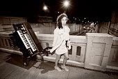 Fille qui transporte son orgue électrique avec un chariot, durant la nuit.  Elle marche sur le trottoir en traversant un pont dans la circulation au centre-ville de Montréal.