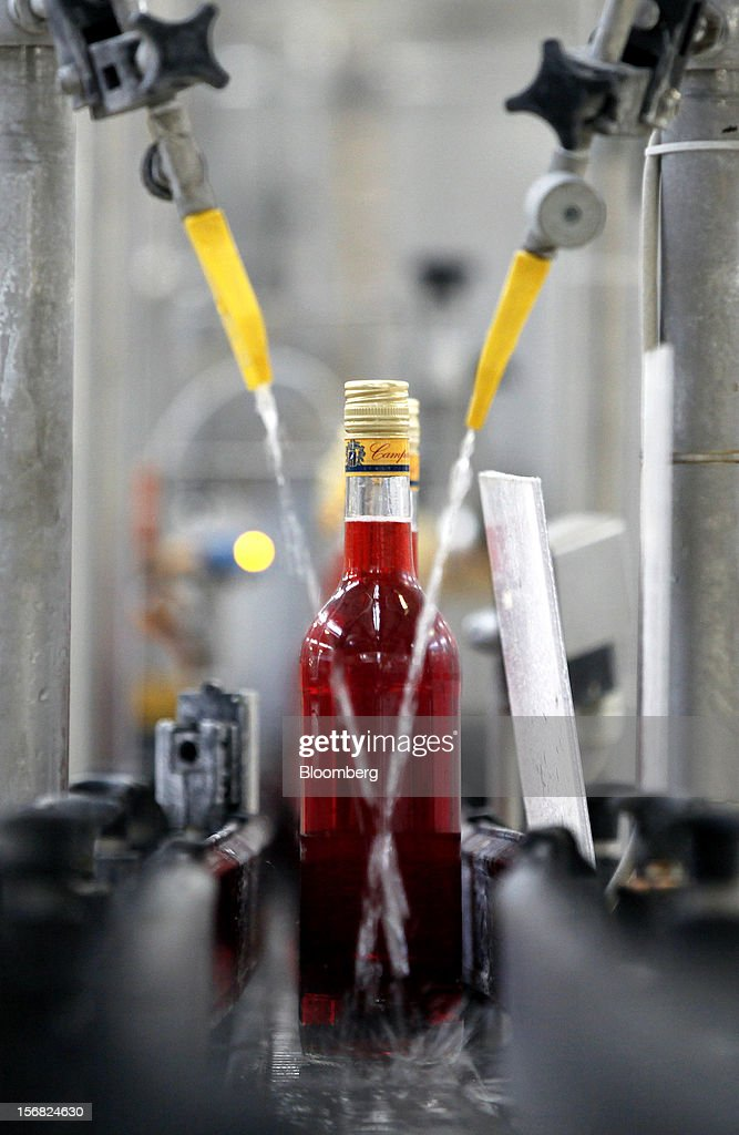 Filled bottles of Campari travel along the production line ahead of labeling at Davide Campari-Milano SpA's factory in Novi Ligure, Italy, on Wednesday, Nov. 21, 2012. Business conditions in Italy, where Campari gets almost a third of annual revenue, are likely to remain volatile in the fourth quarter and early next year, Chief Executive Officer Bob Kunze-Concewitz said. Photographer: Alessia Pierdomenico/Bloomberg via Getty Images
