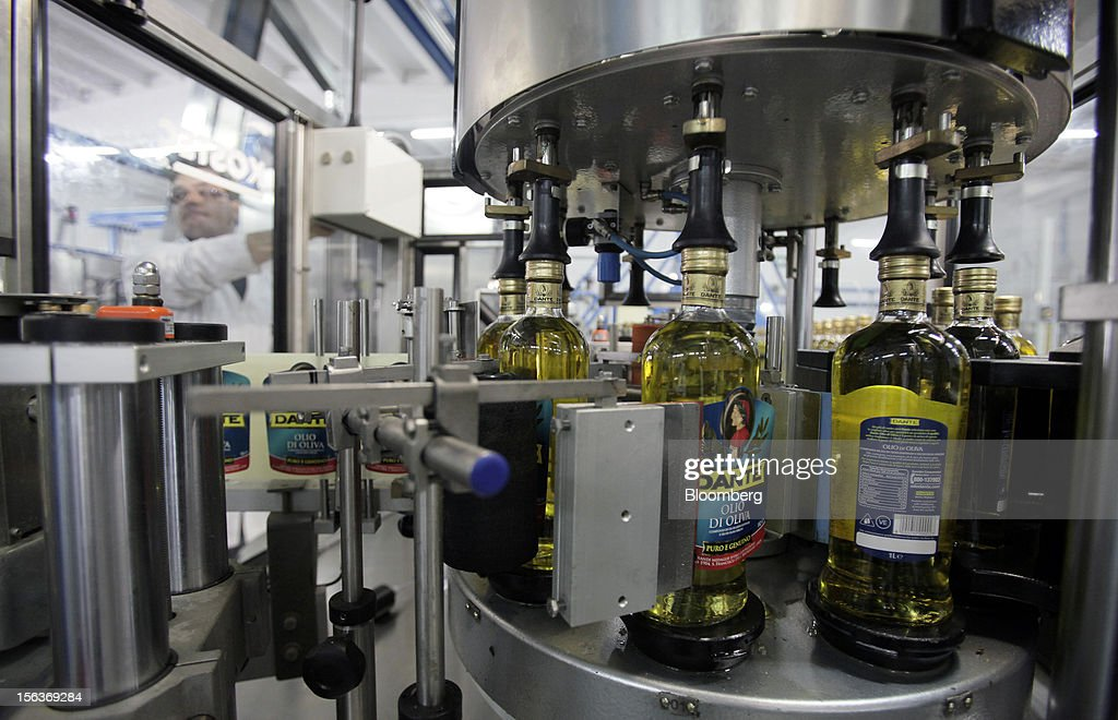 Filled bottles of Dante olive oil pass through a labeling machine as they travel along the production line at Industria Olearia Biagio Mataluni Srl's factory in Montesarchio near Benevento, Italy, on Monday, Nov. 12, 2012. Italian olive-oil exports rose 5.7 percent to a record last year, boosted by demand from the U.S. as well as France and Germany, agricultural-markets researcher Ismea said. Photographer: Alessia Pierdomenico/Bloomberg via Getty Images