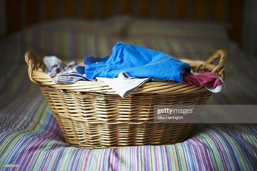 Filled Laundry Basket On Bed : Stock Photo