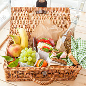 Filled picnic basket with sandwiches and fresh fruits
