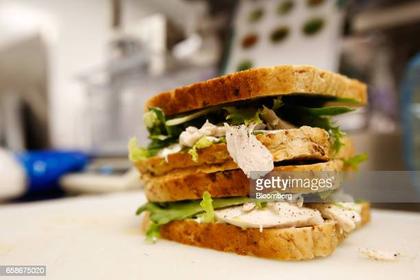 A filled sandwich sits on chopping board waiting to be sliced in the kitchen of a branch of food retailer Pret a Manger Ltd in London UK on Monday...