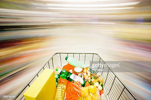 Filled shopping cart races through supermarket creating multicolored motion blur