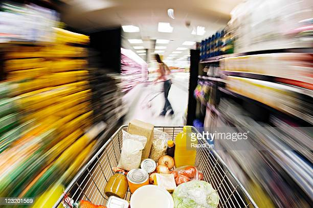 Filled supermarket trolley races down aisle showing extreme motion blur.