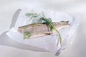 Filleted and dill on white wax paper, close-up