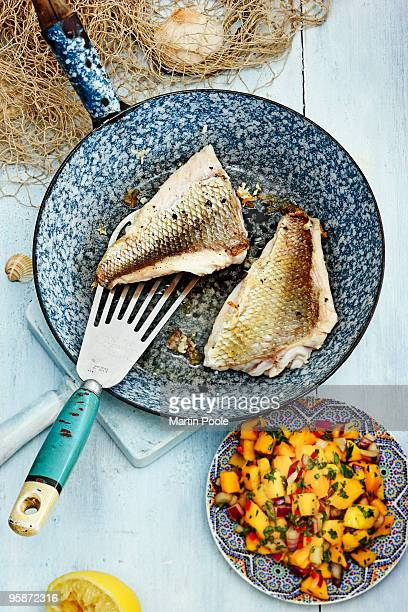 Fillets of sea bass in pan with mango slasa
