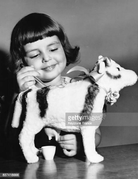 Fillette jouant avec une vache en peluche que l'enfant peut traire à une exposition de jouets à New York EtatsUnis le 7 septembre 1948