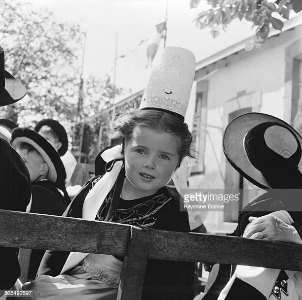 Fillette portant la robe et la coiffe traditionnelles bretonnes sur une charrette à Quiberon France en 1957